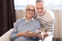 Couples âgés gais tenant une boîte avec le présent Photo stock