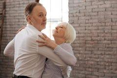 Couples âgés impliqués de danse valsant dans le studio de danse Photo stock