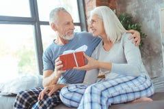Couples âgés joyeux tenant une boîte avec un présent Images libres de droits