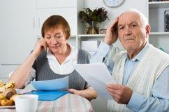 Couples âgés luttant aux bulletins de paie Image libre de droits