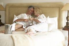 Couples âgés moyens appréciant Champagne dans la chambre à coucher photographie stock