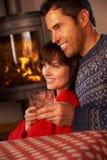 Couples âgés moyens par le feu de bois confortable avec des boissons Photographie stock libre de droits