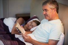 Couples âgés par milieu dans le lit ainsi que le livre de lecture de l'homme Photographie stock libre de droits