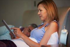 Couples âgés par milieu dans le lit avec la femme à l'aide de la tablette Photos stock