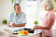 Couples âgés par milieu faisant cuire le repas dans la cuisine ensemble photo stock