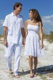 Couples âgés par milieu marchant sur une plage vide images stock