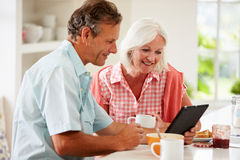 Couples âgés par milieu regardant la Tablette de Digital au-dessus du petit déjeuner Images libres de droits