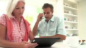 Couples âgés par milieu regardant la Tablette de Digital ayant l'argument banque de vidéos