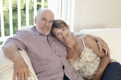 Couples âgés par milieu se reposant sur le divan Images libres de droits