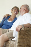 Couples âgés par milieu se reposant sur le divan en osier Image stock