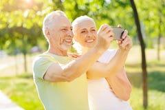 Couples âgés par positif prenant des photos de nature Image libre de droits