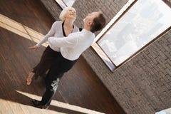Couples âgés qualifiés avec plaisir valsant dans la salle de bal Photo libre de droits