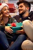 Couples échangeant des boîte-cadeau au réveillon de Noël Photos libres de droits