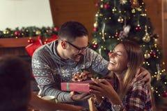 Couples échangeant des cadeaux de Noël photos stock