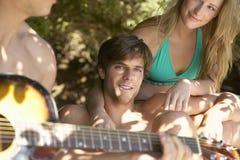 Couples écoutant l'ami jouant la guitare Image libre de droits