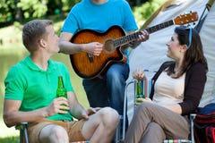 Couples écoutant l'homme jouant la guitare Photos stock