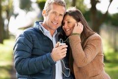 Couples écoutant le MP3 tout en marchant Images stock