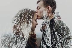 Couples élégants de hippie dans la double exposition avec des branches d'arbre dedans Photo stock