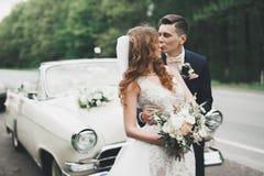 Couples élégants de mariage, jeune mariée, marié embrassant et étreignant sur la rétro voiture Image stock