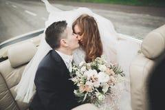 Couples élégants de mariage, jeune mariée, marié embrassant et étreignant sur la rétro voiture Photo libre de droits