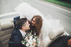 Couples élégants de mariage, jeune mariée, marié embrassant et étreignant sur la rétro voiture Photos stock
