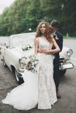 Couples élégants de mariage, jeune mariée, marié embrassant et étreignant sur la rétro voiture Photos libres de droits
