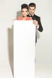 Couples élégants de mode tenant un conseil vide blanc Image stock