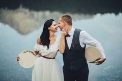 Couples élégants des nouveaux mariés contre le contexte de la montagne images libres de droits