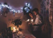 Couples élégants heureux de hippie tenant les feux d'artifice brûlants de cierges magiques Photos stock