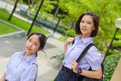 Couples élevés thaïlandais asiatiques mignons d'étudiante d'écolières dans l'uniforme scolaire se tenant avec son ami dans un vis Photographie stock libre de droits