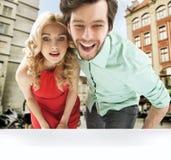 Couples étonnés regardant la fenêtre de shopw Photos libres de droits