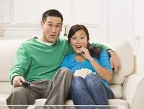Couples étonnés regardant la TV Photos libres de droits