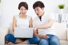 Couples étonnés sur le sofa avec l'ordinateur portable Photos stock