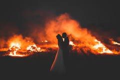 Couples étonnants de mariage près du feu la nuit Images stock