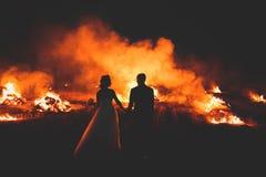 Couples étonnants de mariage près du feu la nuit Image stock