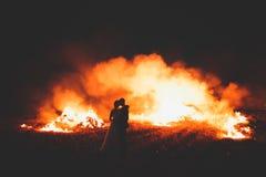 Couples étonnants de mariage près du feu la nuit Photos stock