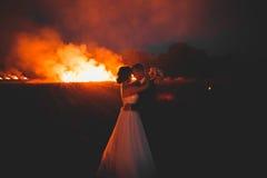 Couples étonnants de mariage près du feu la nuit Images libres de droits