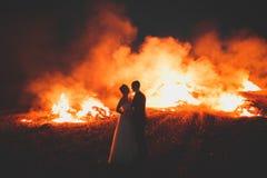 Couples étonnants de mariage près du feu la nuit Image libre de droits