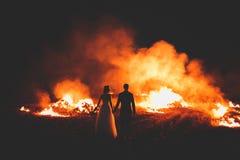 Couples étonnants de mariage près du feu la nuit Photographie stock libre de droits