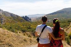 Couples étreignant contre le paysage de montagne Photographie stock libre de droits