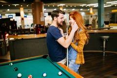 Couples étreignant dans la barre de billard Image stock