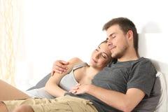 Couples étreignant et dormant dans un lit Photos libres de droits