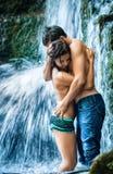 Couples étreignant et embrassant sous la cascade à écriture ligne par ligne Image stock