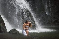 Couples étreignant sous des cascades à écriture ligne par ligne Photographie stock libre de droits