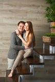 Couples étreignant tout en se reposant sur l'escalier Images stock