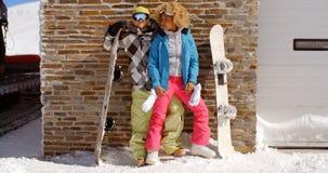 Couples étroits posant avec des surfs des neiges contre le garage Photographie stock