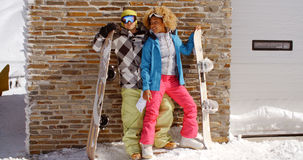 Couples étroits posant avec des surfs des neiges contre le garage Image libre de droits