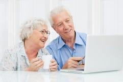 Couples aînés à l'ordinateur portatif Photographie stock libre de droits