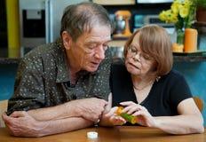 Couples aînés à la maison discutant le médicament Photo stock