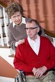 Couples aînés à la maison, homme dans le fauteuil roulant Photo libre de droits
